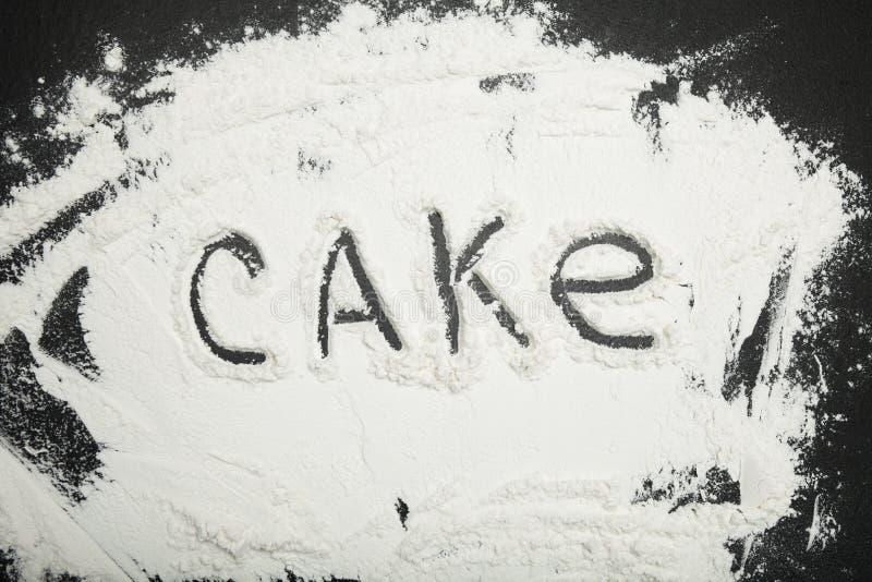 Formułuje tort pisać na białej mące, czarny tło fotografia stock
