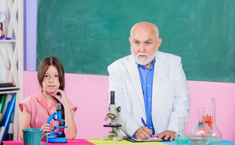 formu?a mała dziewczyna z mężczyzny adiunkta nauki chemią nauki sala lekcyjna używa powiększać - szkło mikrosekunda laboratorium zdjęcie royalty free