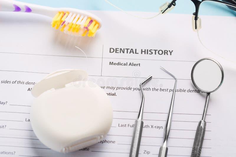 Formulário da história dental com os instrumentos, o espelho e fio dental dentais de aço profissionais perto da escova de dentes  fotografia de stock