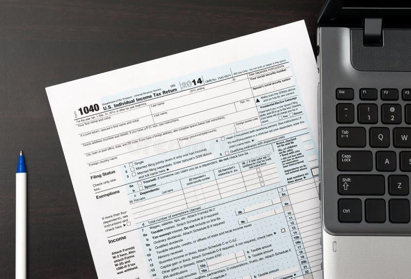 Formulário de declaração de rendimentos individual 1040 dos E.U. em uma tabela com portátil e pena fotos de stock royalty free