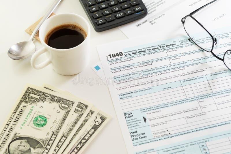 Formulário de declaração de rendimentos da renda com um copo do café preto, do dinheiro e dos vidros na tabela imagem de stock royalty free