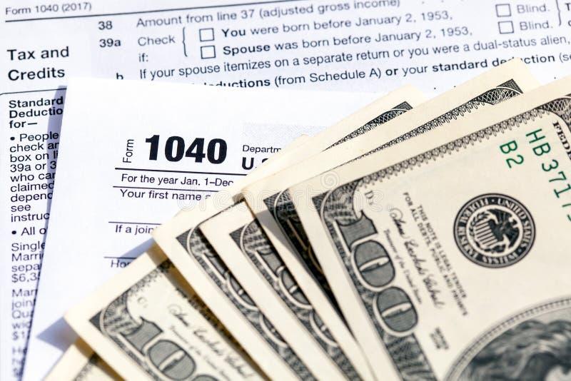 Formulário de declaração de rendimentos da renda do indivíduo dos EUA 1040 com cem notas de dólar foto de stock royalty free