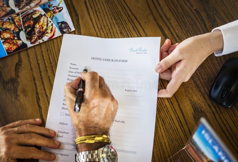 Formulário de enchimento do registro do hotel do convidado fotografia de stock