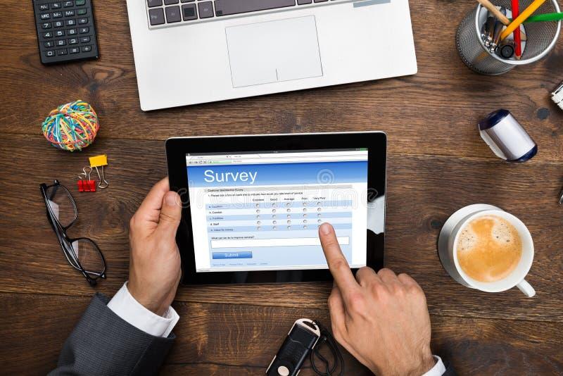 Formulário de Filling Online Survey do homem de negócios imagem de stock royalty free