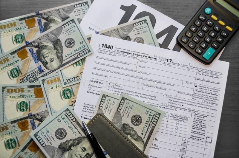 Formulário de imposto 1040, caderno, calculadora, pena e dólares fotografia de stock
