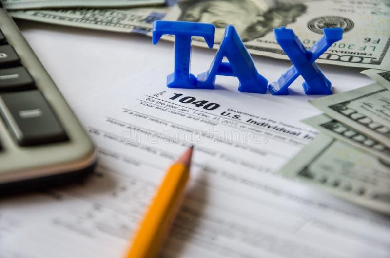 Formulário de imposto 1040, calculadora, lápis e dólares em um fundo branco fotos de stock royalty free