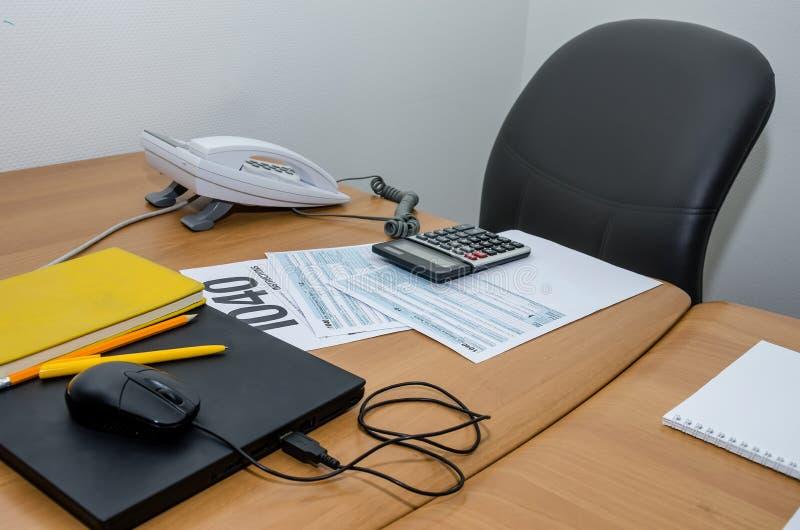 Formulário de imposto 1040, calculadora, pena do caderno i na mesa de escritório imagens de stock