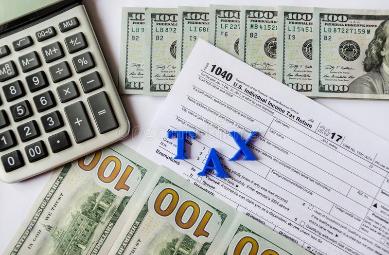 Formulário de imposto 1040, dólares, calculadora em um fundo branco foto de stock