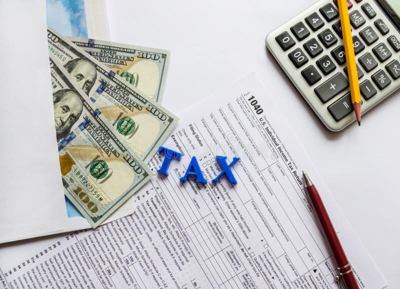 Formulário de imposto 1040, dólares, calculadora, pena e lápis imagens de stock