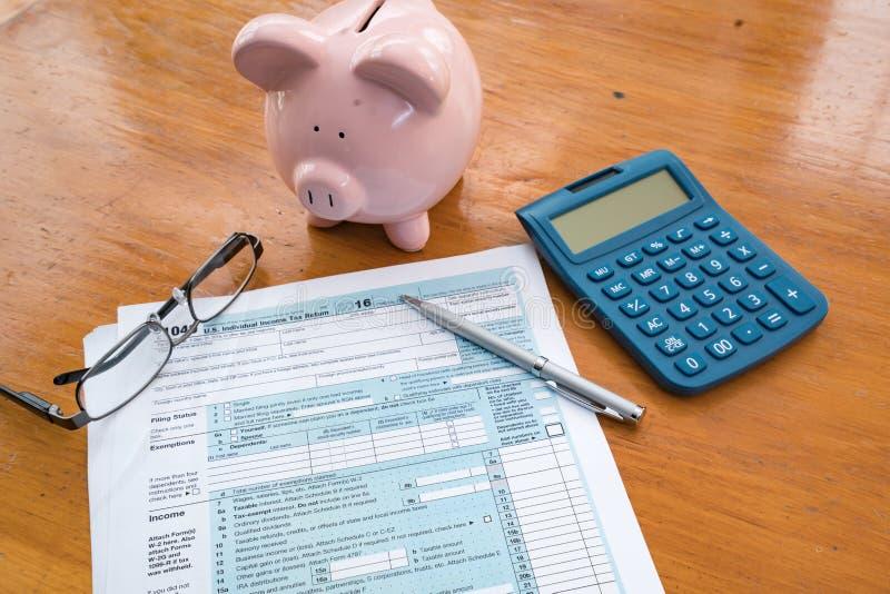 Formulário de imposto do IRS com mealheiro e calculadora imagens de stock royalty free