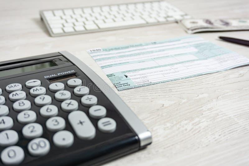 Formulário de imposto dos E.U. ao lado do teclado de computador, da calculadora e do formulário de imposto 1040 o imposto forma-n imagem de stock royalty free