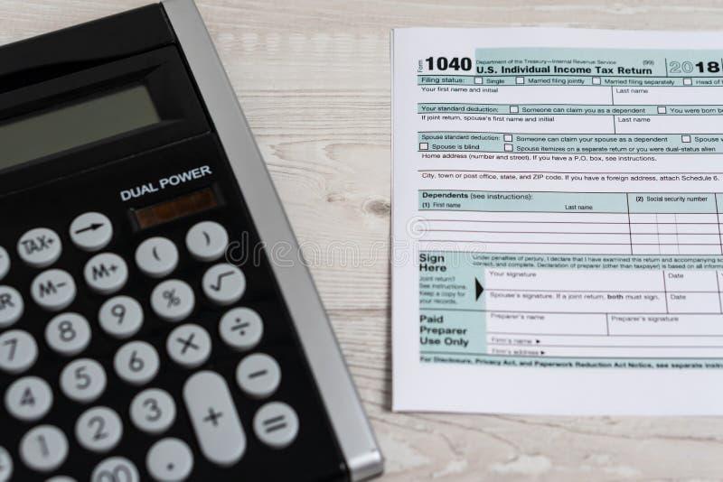Formulário de imposto 1040 dos E.U. com calculadora e conceito branco do negócio do documento EUA da lei do formulário de imposto fotos de stock royalty free