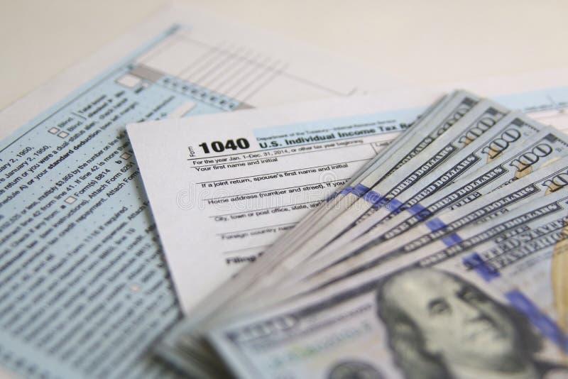 Formulário de imposto 1040 dos E.U. com 100 notas de dólar novas dos E.U. fotografia de stock