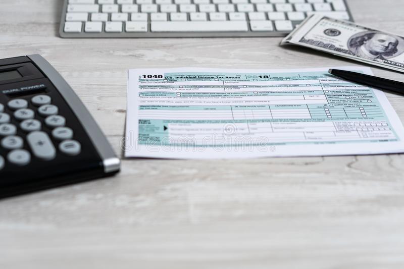 Formulário de imposto 1040 dos E.U. com pena, calculadora e notas de dólar conceito branco do negócio do documento EUA da lei do  imagens de stock royalty free