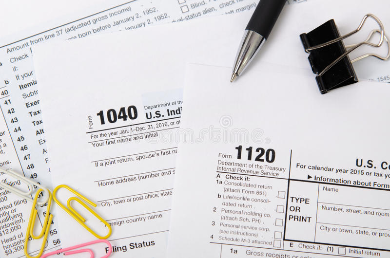 Formulário de imposto 1040 dos E.U., 1120 na mesa fotos de stock
