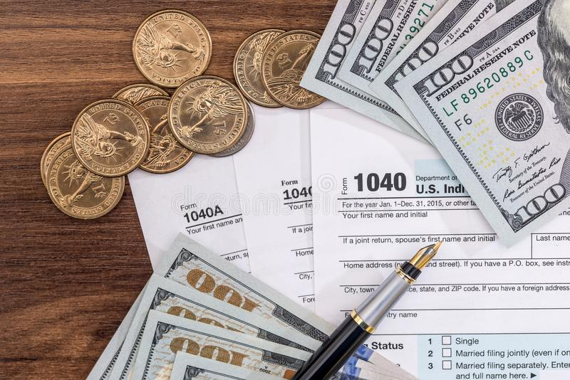 Formulário de imposto de 1040 E.U. com contas e moedas do dolllr fotografia de stock