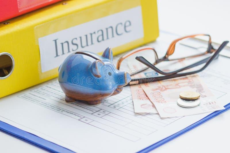 Formulário, mealheiro, vidros e dinheiro do seguro fotografia de stock royalty free