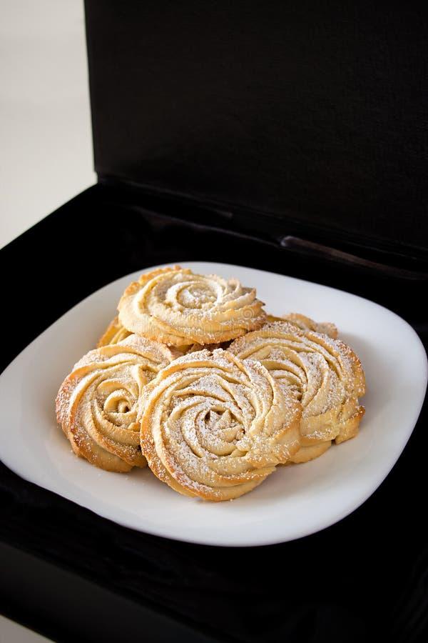 Formulário redondo das rosas das cookies de biscoito amanteigado Fundo preto imagem de stock