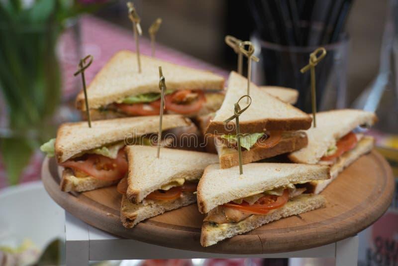 Formulário triangular fresco dos sanduíches de clube com tomate em uma placa de desbastamento de madeira redonda em uma tabela em imagem de stock royalty free