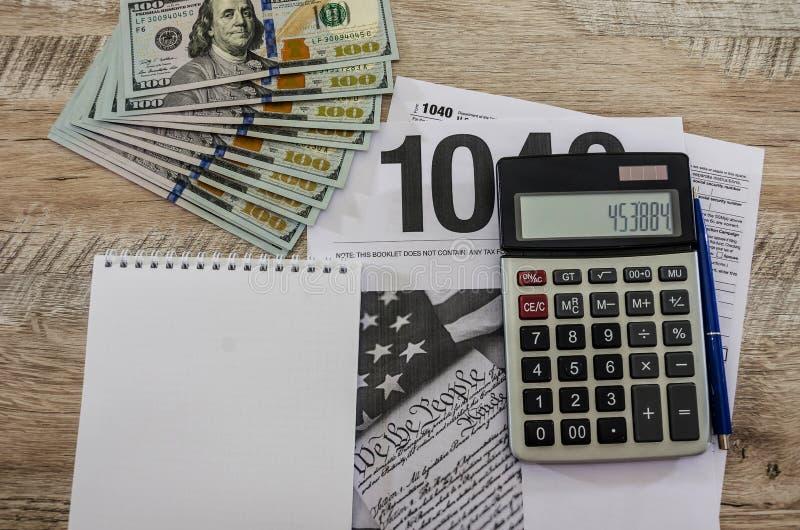 Formulários de imposto 1040, calculadora, dólares, bloco de notas e pena em um fundo de madeira foto de stock
