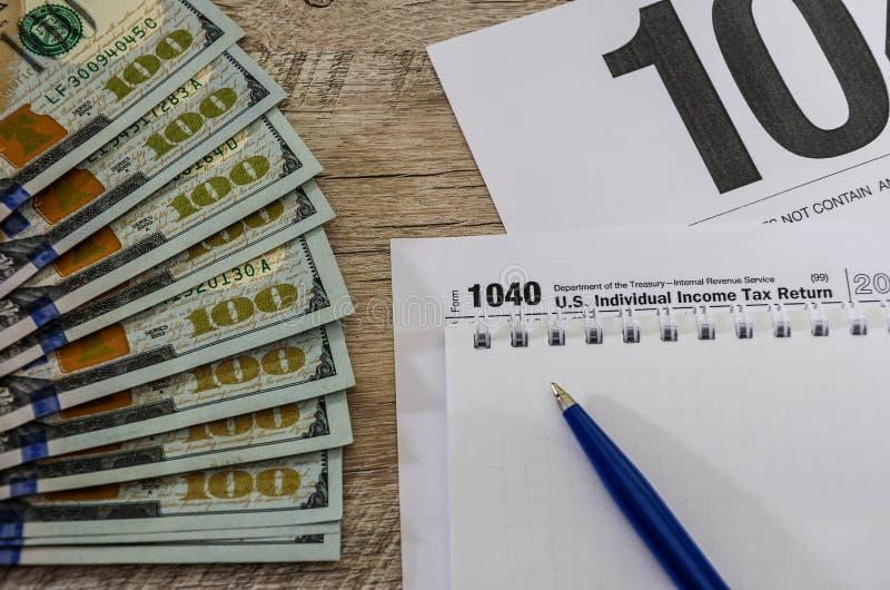Formulários de imposto 1040, dólares, caderno e pena no fundo de madeira imagem de stock royalty free