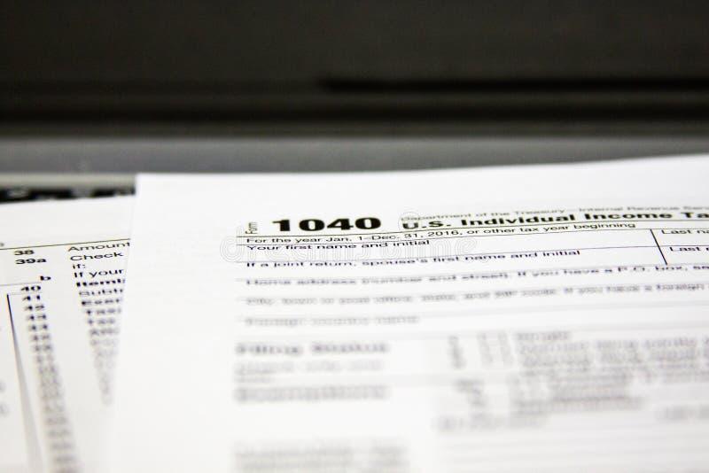Formulários de imposto em um portátil imagem de stock
