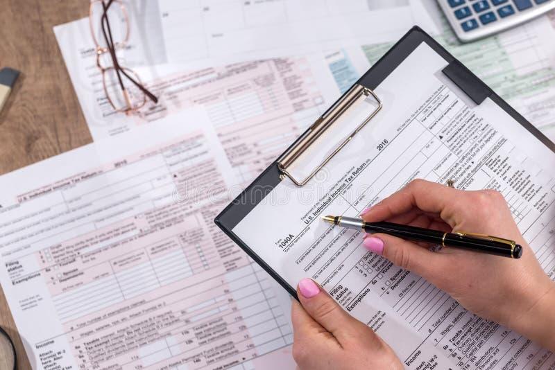 Formulários de imposto de enchimento da mulher foto de stock