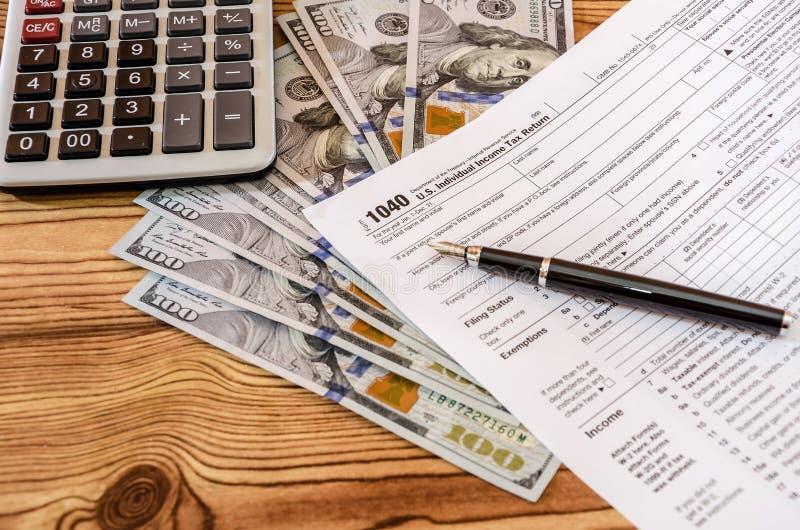 Formulários de imposto 1040, pena, calculadora e dólares em uma tabela de madeira imagens de stock royalty free