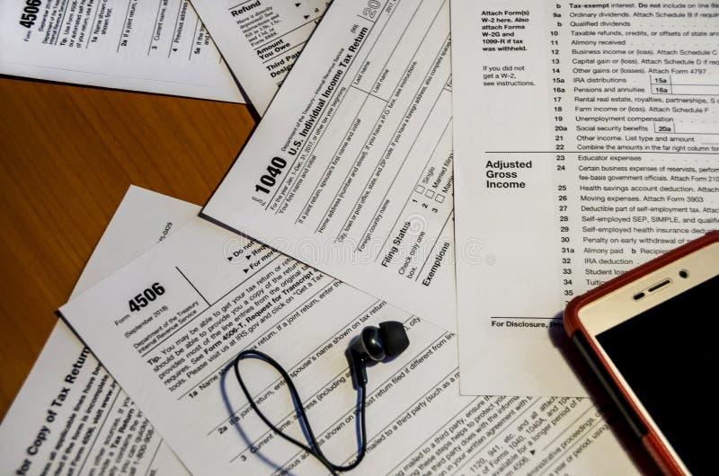 Formulários 4506 e 1040 no close-up da tabela, e peça do smartphone imagem de stock royalty free