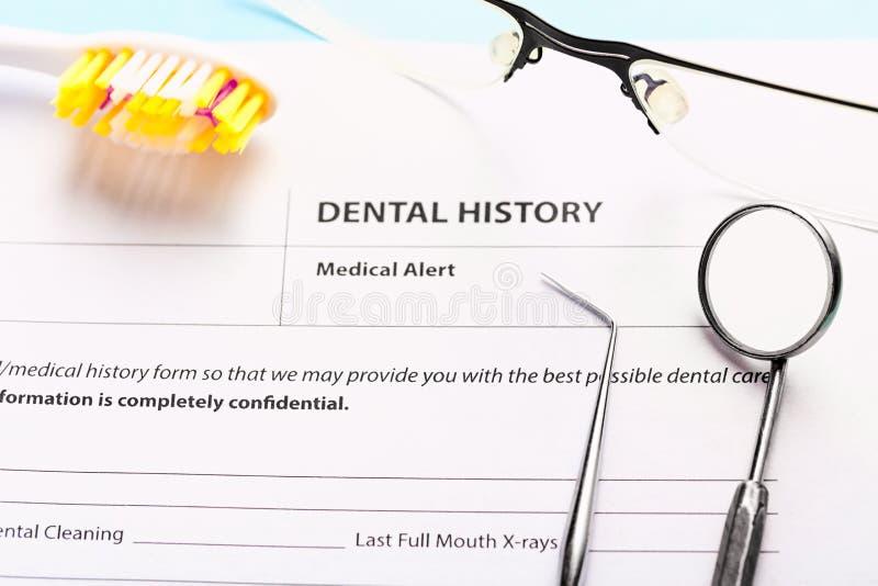 Formul?rio da hist?ria dental com os instrumentos dentais de a?o profissionais, o espelho perto da escova de dentes e os vidros S foto de stock