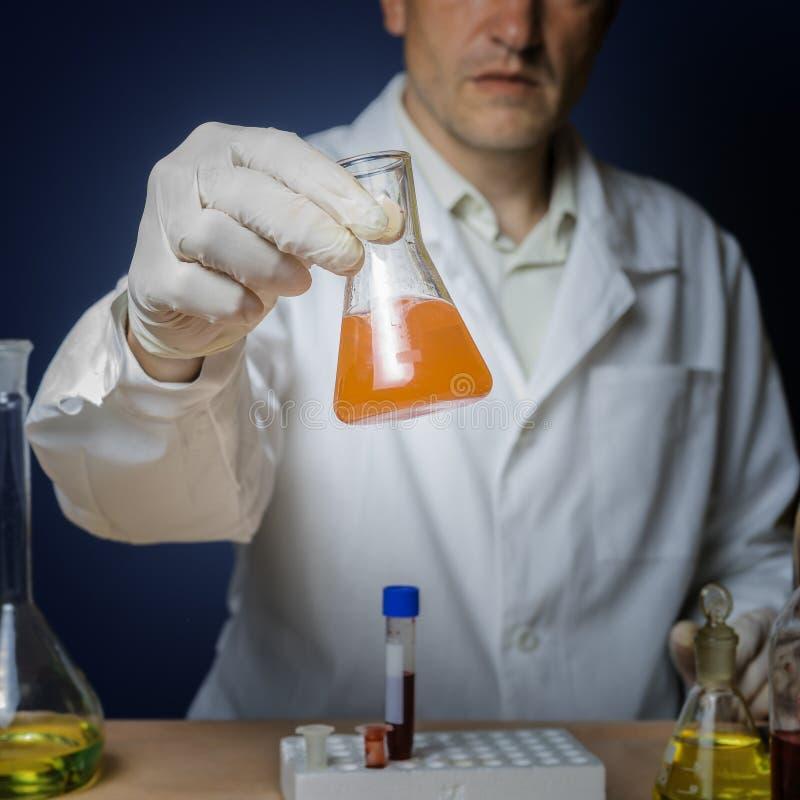 Formulação química para a medicina, pesquisa do laboratório O assistente de laboratório guarda uma garrafa em sua mão fotografia de stock royalty free
