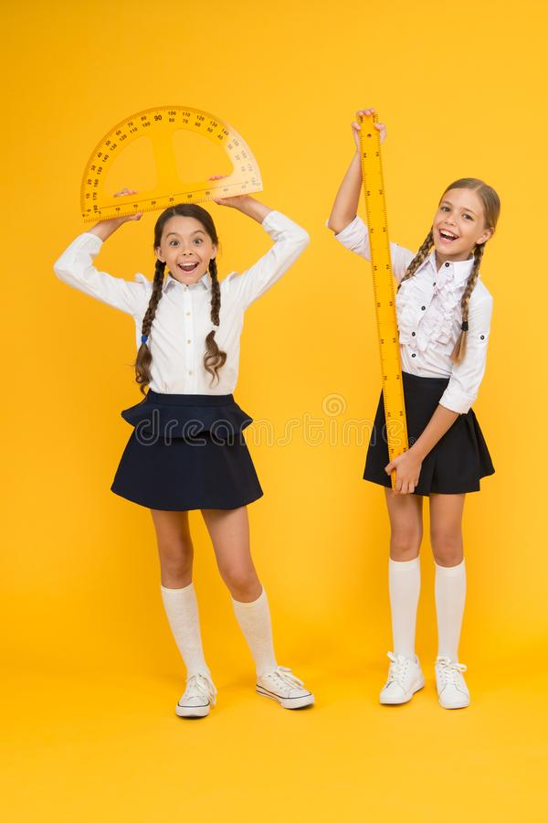 Formula. back to school. Maths and geometry. Kids in uniform at yellow wall. friendship and sisterhood. happy small. Girls study mathematics. students use stock images