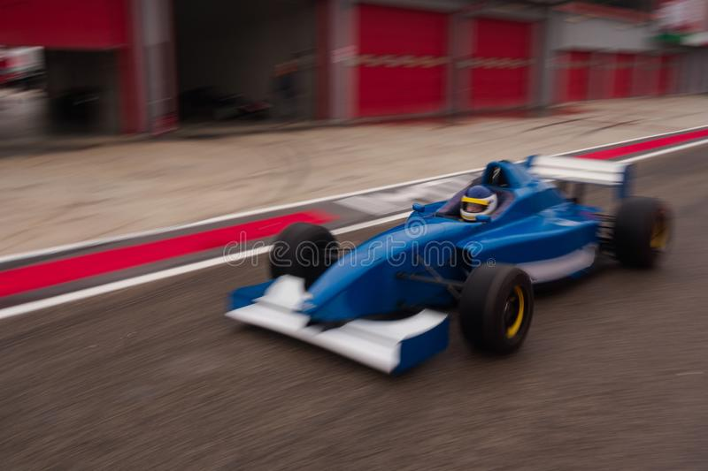 Formula car is approaching the track from the pitlane. Blue formula car is approaching the track from the pitlane stock image