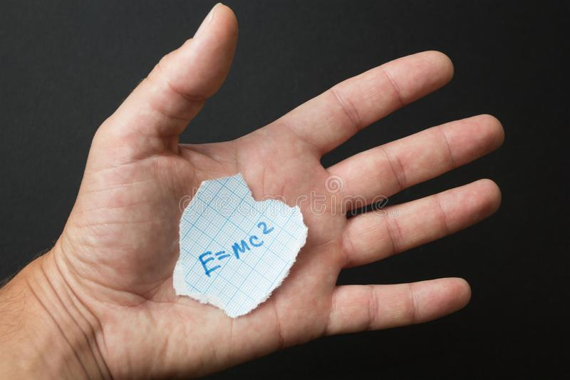 The formula E = mc2 in the hand stock image