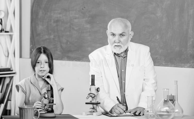 Formula. small girl with man tutor study chemistry. science classroom. use magnifying glass. Microscopy. Laboratory stock photo