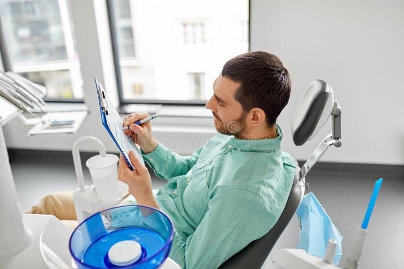Formulaire de demande remplissant patient à la clinique dentaire image stock