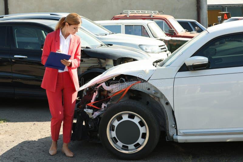 Formulario de demanda de relleno del agente de seguro cerca del coche quebrado fotos de archivo