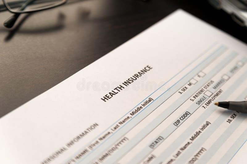 Formulario de inscripción del seguro médico en una tabla de madera imagenes de archivo