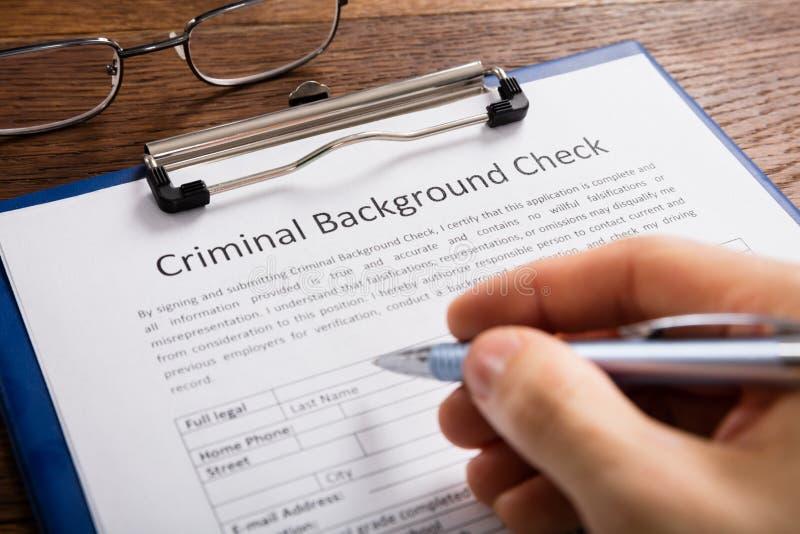 Formulario de inscripción de Person Filling Criminal Background Check imagen de archivo