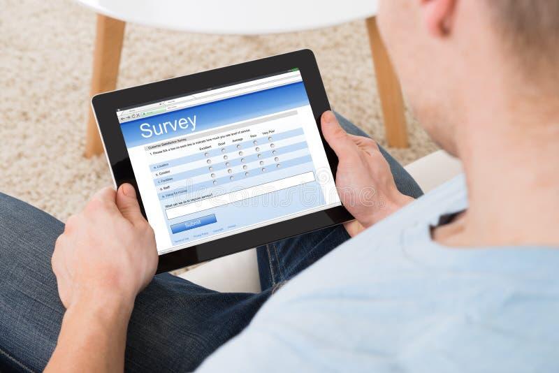 Formulario de la encuesta sobre el relleno del hombre en línea en la tableta de Digitaces en casa foto de archivo libre de regalías