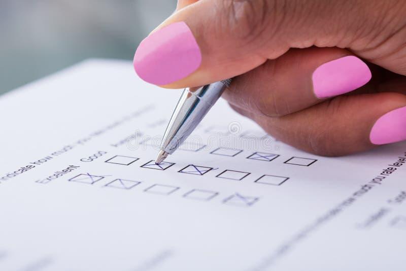 Formulario de relleno de la encuesta a los clientes de la mano de la empresaria fotos de archivo