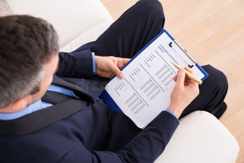 Formulario de relleno de la encuesta a los clientes del hombre de negocios imagenes de archivo