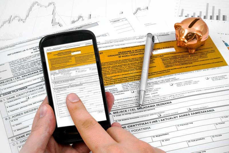Formulario del impuesto sobre la renta del pulimento del relleno del hombre en móvil fotografía de archivo