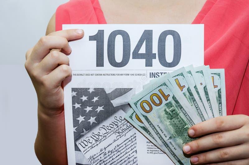 1040 formularzy podatkowych i dolarów w rękach kobiet Biznesmenka posiadająca formularz podatkowy w swoich rękach Zbliżenie zdjęcie stock
