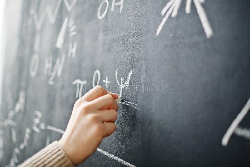 Formule d'écriture de main sur le tableau noir photo stock