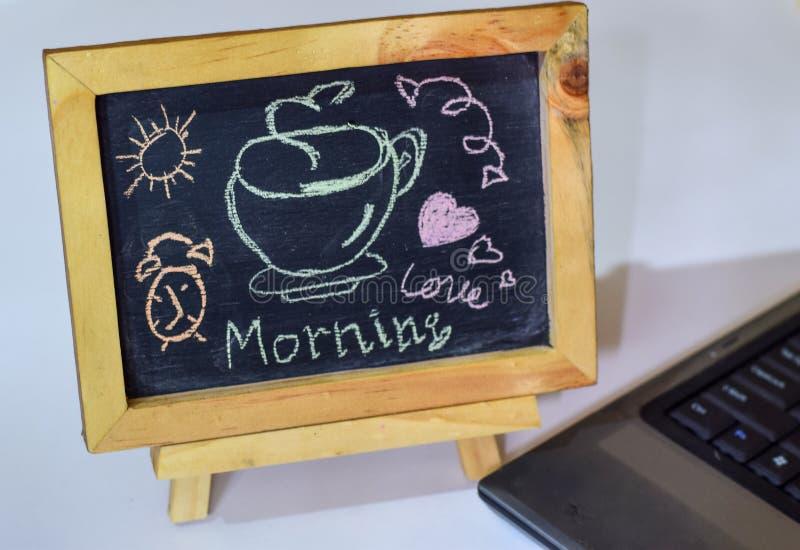 Formulera kaffe för den bra morgonen som är skriftligt på en svart tavla på den och smartphonen, bärbar dator arkivbilder