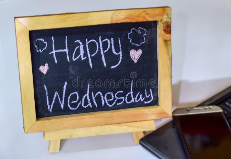 Formulera lyckliga onsdag som är skriftlig på en svart tavla på den och smartphonen, bärbar dator arkivfoton