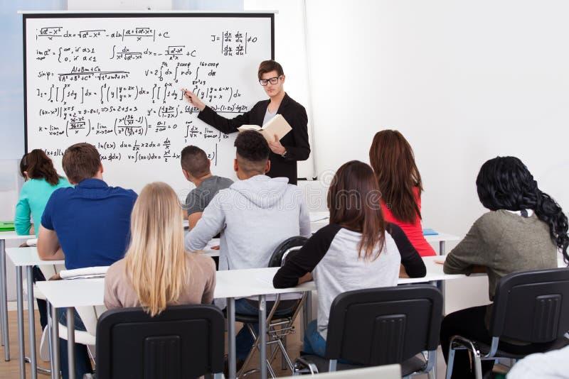 Formules de enseignement de maths de professeur aux étudiants universitaires photographie stock libre de droits