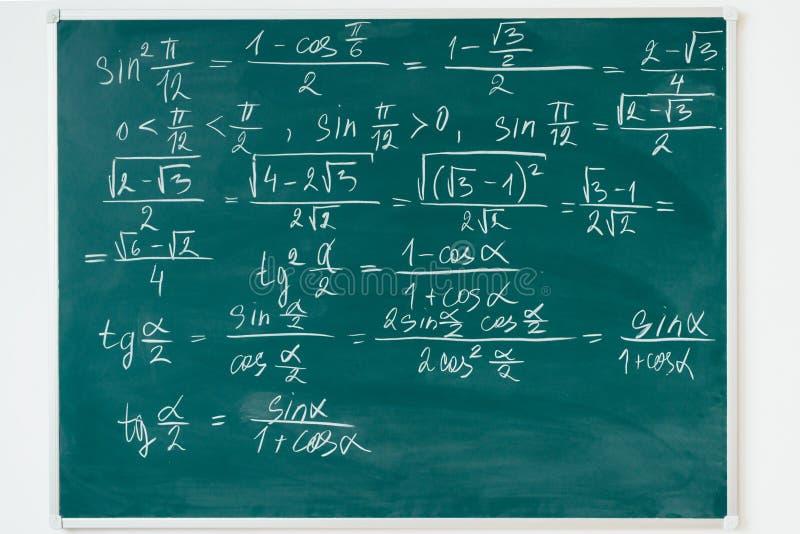 Formules de maths écrites par la craie blanche sur le tableau noir photos stock