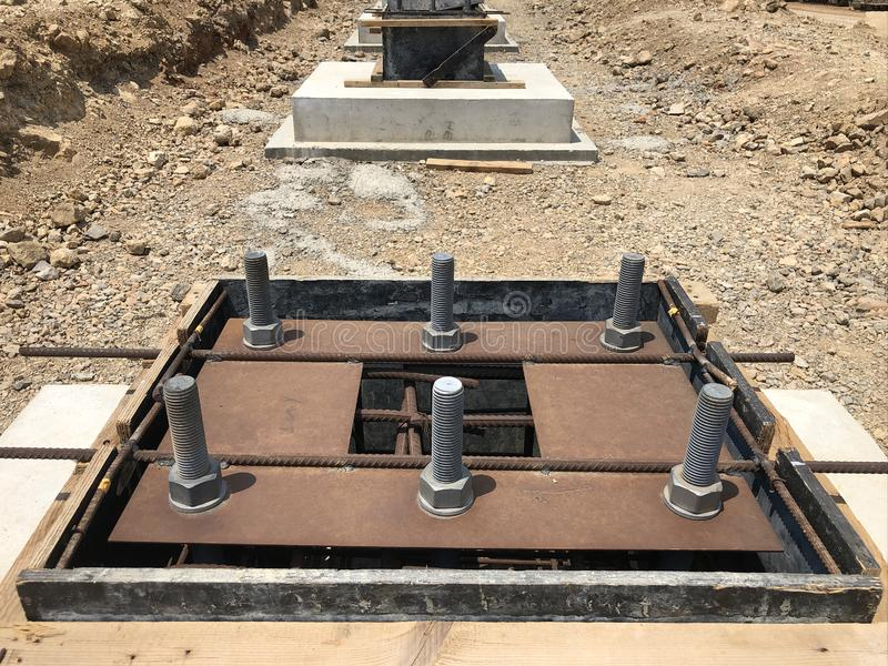 Formwork and reinforcement of concrete foundation with metal anchor bolts designed for the installation of metal columns. Formwork and reinforcement of concrete royalty free stock images